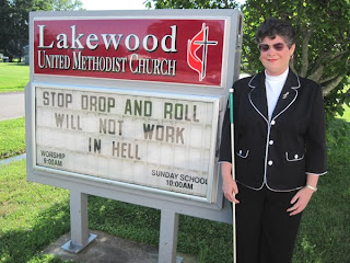 Laurel standing by Lakewood UMC sign