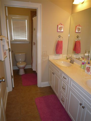jack n jill bath with two sinks and door to toilet and bathtub room