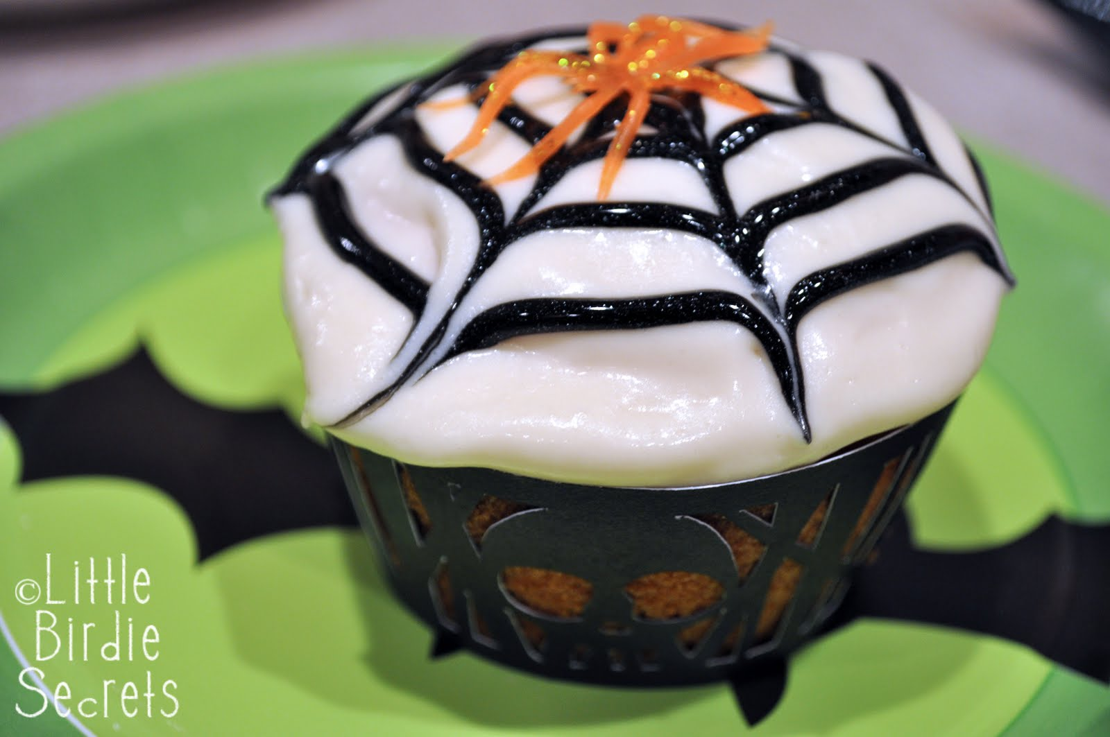 Super-easy white-chocolate spider web toppers appear to float, Houdini-like, over chocolate cupcakes. Get the spiderweb cupcake recipe now!