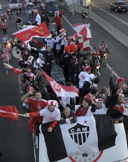 Torcida do Estudiantes com a bandeira do Atlético Mineiro.
