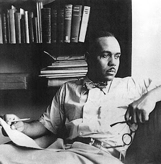 African American writer Ralph Ellison in front of a bookcase