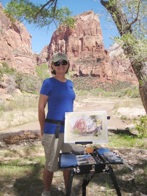 Art collector Kathy Richards admires Roland Lee's watercolor painting at the Footsteps of Thomas Moran Plein Air Invitational in Zion National Park