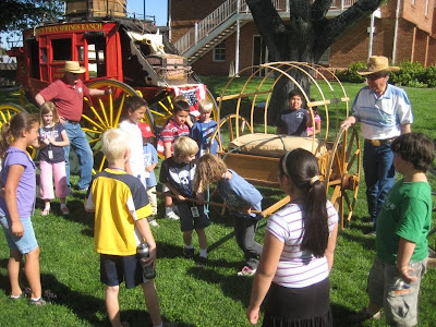 Sons of Utah Pioneers member Dean Terry and school children try out a pioneer hand cart at Cotton Days Festival