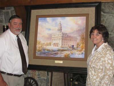 Joyce and Grant Lee with their new painting of the Nauvoo Temple by Roland Lee