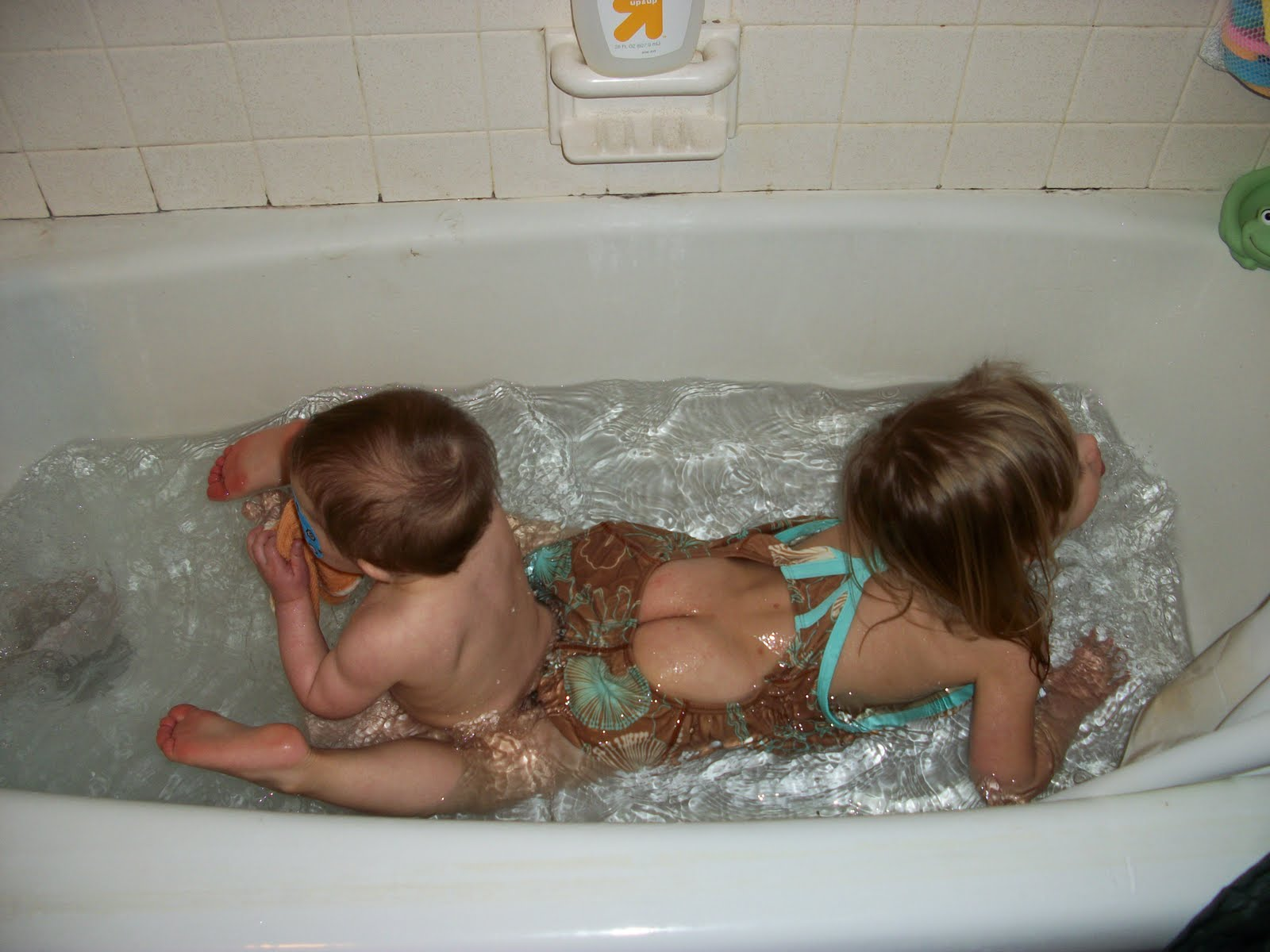 A little boy and girl are in a bathtub, and are  because they