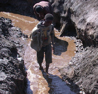 Children trudging through an open pit mine.