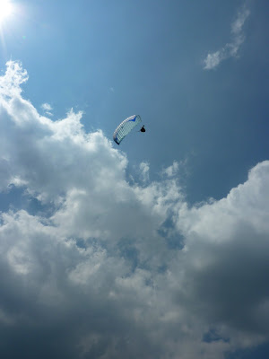 Paraglider against blue sky with fluffy clouds