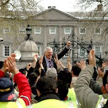Joe Higgins celebrando victoria con trabajadores inmigrantes