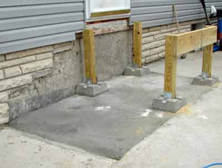 A start to the new wooden back steps. With newly poured cement slab the pillar posts are set in place.