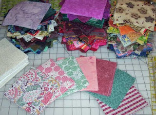 There are a lot of five inch quilt squares here to sort through. This is my start at color coordinating them - some of the more old fashioned ones.