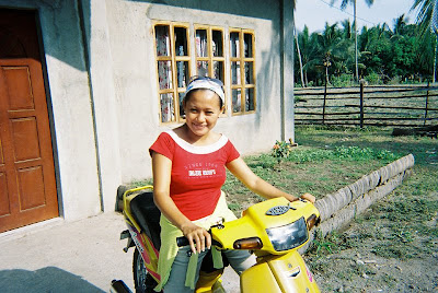 Marilyn posing on her motorcycle outside her home in Bacong, Philippines