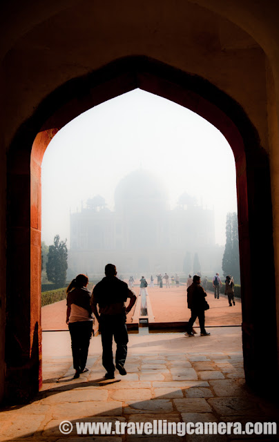 A Quick visit to Humayun's Tomb during a foggy day of Delhi-Winters !!! : Posted by VJ SHARMA on www.travellingcamera.com : Humayun's Tomb is a huge area having multiple Mughal architectural forms. It is located in East-Nizamuddin area of Delhi, India...This area has main tomb of the Emperor Humayun as well as numerous others... The complex is a World Heritage Site and the first example of this type of Mughal architecture in India...The architecture is similar to Taj Mahal.This weekend we planned to visit Humayun's Tomb during early morning and then reach Surajkund Fair by 11:30 am... Our morning started late and plan got delayed.. We reached  Humayun's Tomb at 09:45 am and then thought of having a quick round and move towards Surajkund Fair which is a famous handicraft Mela in Faridabaad... It was a foggy Saturday and I was little disappointed... Here are few Photographs I clicked during this weekend.. Have a look !!!I think these tourists are also disappointed like me because they can't have their photograph in front of Humayun's Tomb.. of course, they can click one but an explanation is required about the place :) ... So the faded architectural form in the background is Humayun's Tomb... In this complete post, there is no clear Photograph of the Tomb, so you can check out the real place @ http://phototravelings.blogspot.com/2009/01/humayuns-tomb-delhi.htmlSunlight touching lush green grounds of Humayun's Tomb after struggling with bunch of trees...I have never shot these kind of light streaks in a better way :( .... Many times I tried but not very happy with the final results... Of course, I have a new excuse this time :