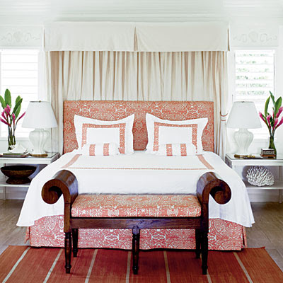 In each of the bedrooms, Meg embellished simple white coverlets, shams, and bolster pillows with embroidered trim that lends a little graphic weight to the pieces by outlining their shapes.