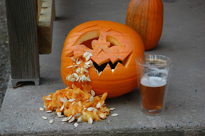 Jack-o-lantern, next to a glass of beer, throwing up.
