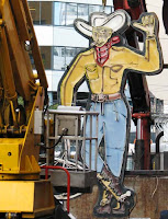 The neon cowboy being removed from Dixon St