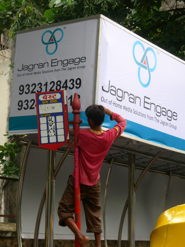 hoarding being fixed on a bus stop in mumbai by kunal bhatia