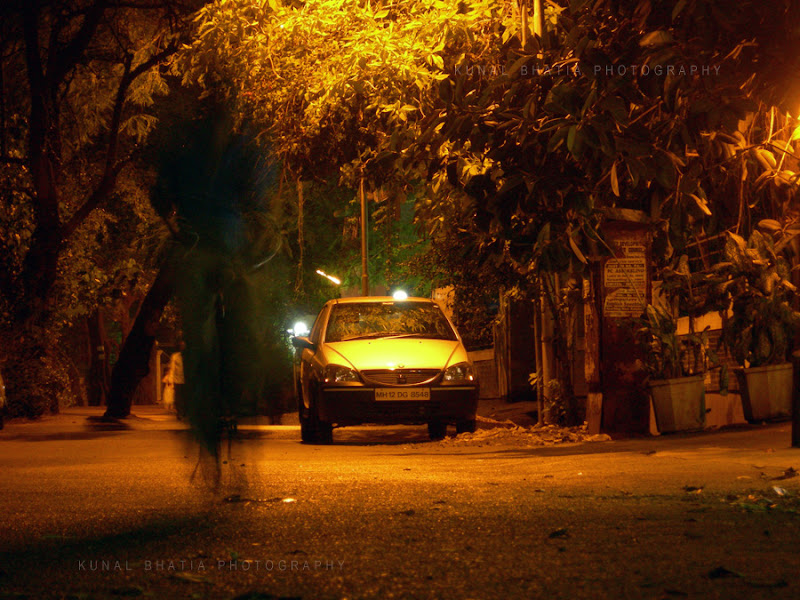 slow shutter speed cyclist moving fast blurred ghostly night street photo in mumbai by kunal bhatia
