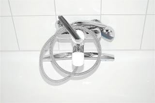 primer plano de ducha cromada tipo teléfono sobre fondo de cerámica y baldosas blancas