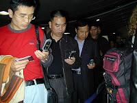 Geschäftsleute in Hong Kong, alle mit Handy in linker Hand