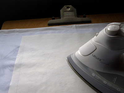 An iron pressing a piece of paper onto a length of white fabric.