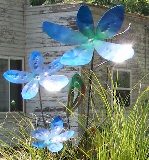 Blue metal art flowers glistening in the sun