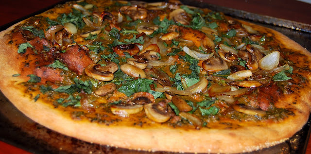 Pizza topped with mushrooms and a basil sauce. A vegan recipe