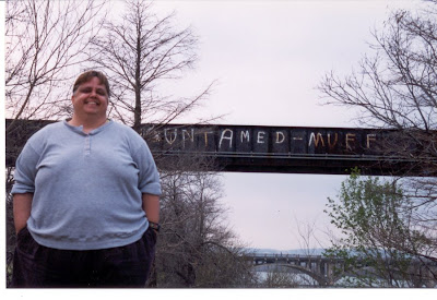 Maggie in front of Untamed Muff graffiti on railroad bridge over the Colorado River, Austin, Texas, 1999