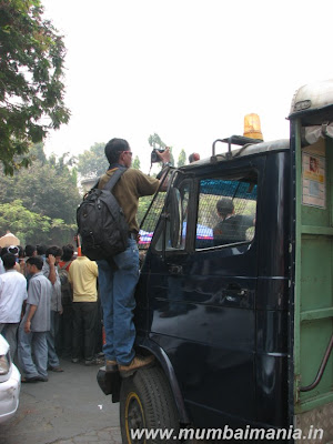 a person standing on the tyre of a police van
