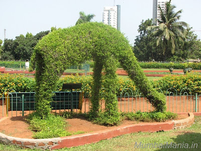 Giraffe eating grass plant sculpture at Mumbai garden