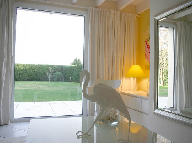 La terrasse blanche et le sol du salon de part et d'autre de la baie contribue à agrandir l'espace.