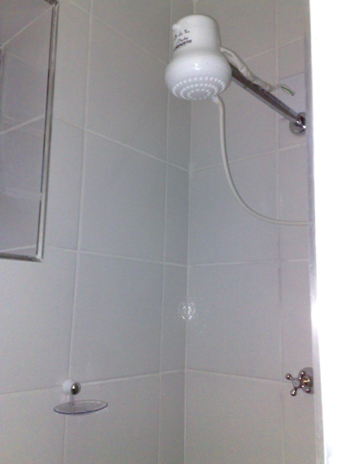que era meio banheiro com um chuveiro improvisando cabide  #5C4C4B 1200 1600