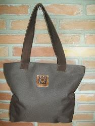 Bolsa com aplicação de peça em cerâmica esmaltada