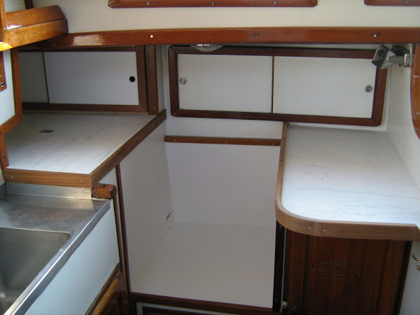 Install Corian counters and teak fiddles