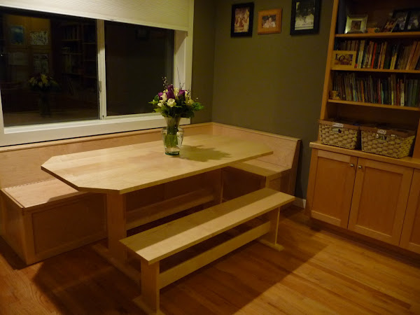 Custom built table and L shaped bench with storage below.