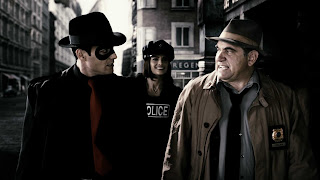 The Spirit (Gabriel Macht, left), Officer Morgenstern (Stana Katic) and Commisioner Dolan (Dan Lauria)keep the streets of Central City safe for honest citizens. It's too bad they couldn't stop Frank Miller.