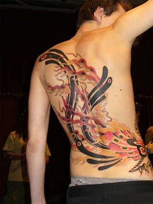 Mythical trobal phoenix bird tattoo on stomach.
