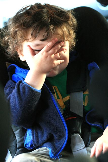 boy covering his face in car seat