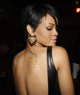 Girl Celebrity Tattoos From Rihanna on Back With Star Design