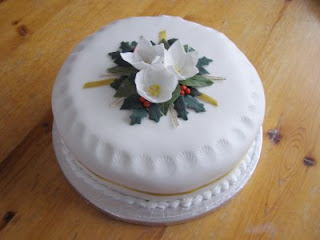 A round cake covered in white icing with flowers and holy on top