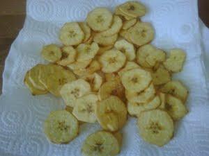 Rodajas de plátano frito escurriendo en papel absorbente.