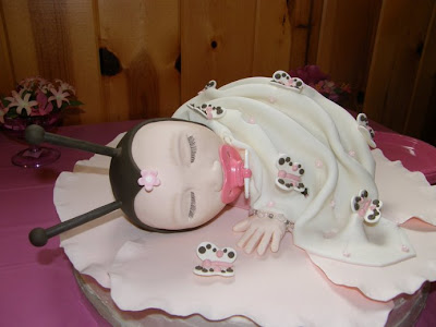 baby shower cake was made to resemble the anne geddes style of baby