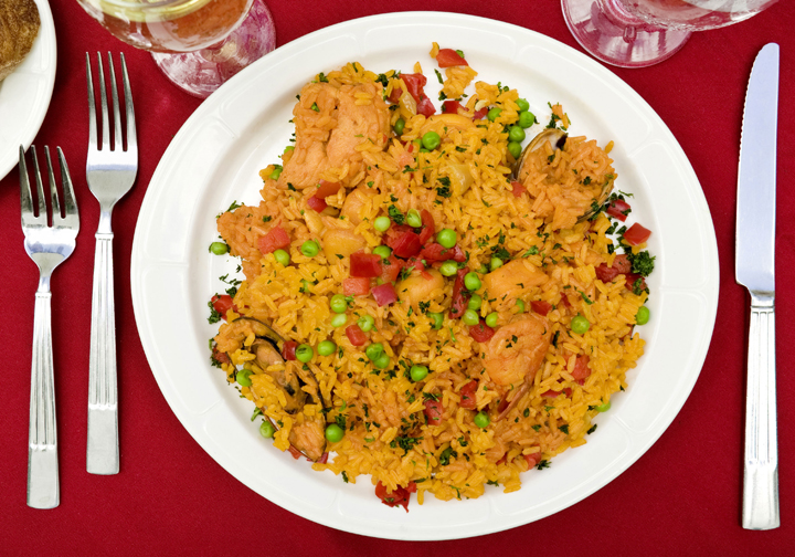 "Arroz con pollo[ah-ROHS con POH-yoh]Literally ""rice with chicken ..."