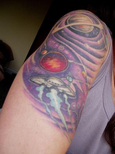 Old school UFO tattoo in outer space.