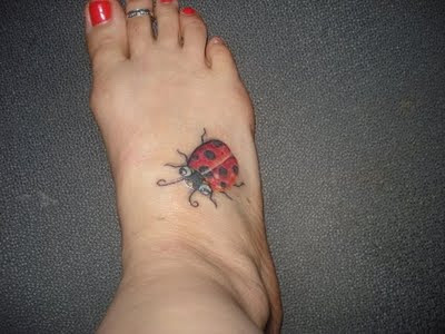 Big ladybug tattoo on foot.