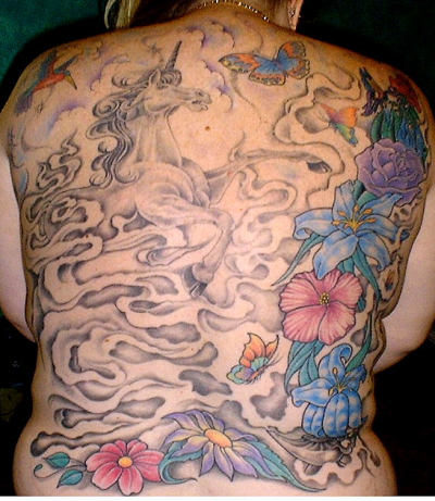 Mythical back piece tattoo with unicorn and flowers.