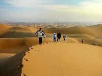 Pessoas caminhano nas dunas iranianas