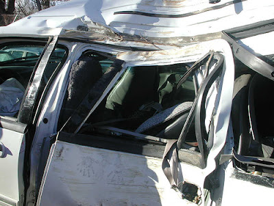 Closeup of White SUV badly crumpled left side passenger panel and broken window intruding into the passenger compartment. The roof is crumpled. Black handprints are below the broken window.