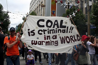protesters with a banner that says Coal is Criminal in a Warming World
