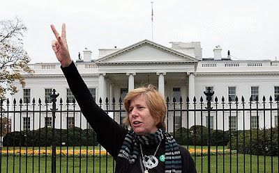 Cindy Sheehan in front of the White House making a peace sign