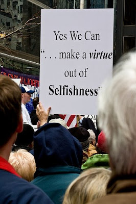 protester with sign saying yes we can make a virtue out of selfishness